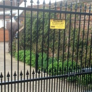 image of black metal gate with warning